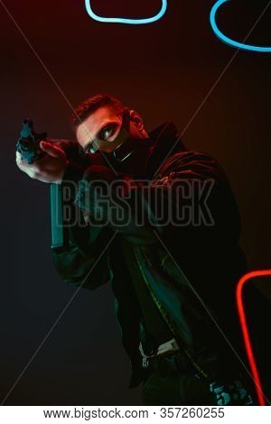 Bi-racial Cyberpunk Player In Protective Mask Aiming Gun Near Neon Lighting On Black