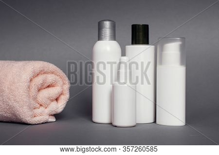 Closed Cosmetic Or Hygiene Bottles Of Gel, Serum, Lotion, Shampoo. Gray Background
