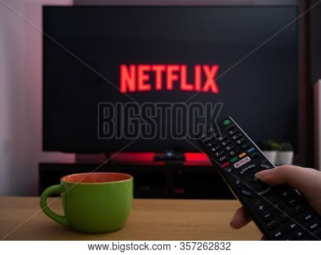 Uk, March 2020: Tv Television Netflix Logo On Screen With Remote Control In Home