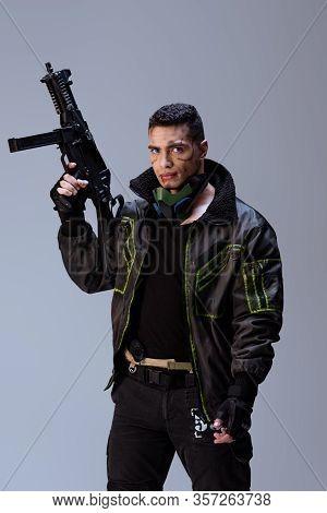 Armed Bi-racial Cyberpunk Player Holding Gun Isolated On Grey