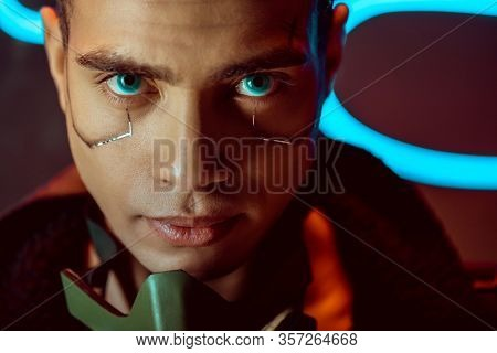 Handsome And Bi-racial Cyberpunk Player Looking At Camera Near Neon Lighting