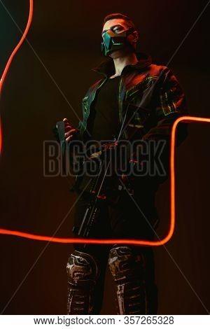 Dangerous Bi-racial Cyberpunk Player In Protective Mask Holding Gun Near Neon Lighting On Black