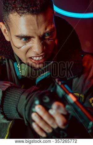 Selective Focus Of Angry Bi-racial Cyberpunk Player With Metallic Plates On Face Holding Gun