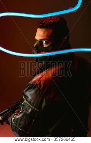 Selective Focus Of Bi-racial Cyberpunk Player In Protective Mask Holding Gun Near Blue Neon Lighting