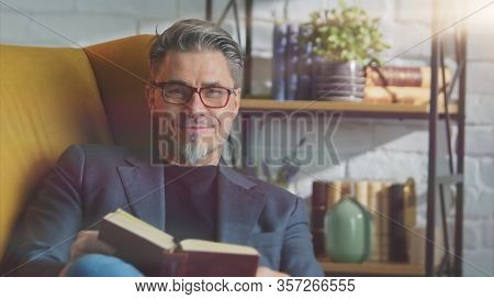 Stay at home - Older white man in glasses reading book at home sitting in armchair in cosy room.