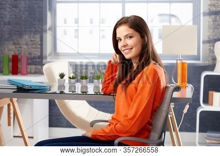 Stay at home - Happy young woman sitting at home, smiling in orange pullover.