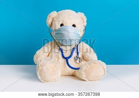 Cute Teddy Bear Doctor With Protective Medical Mask And Stethoscope. Concept Of Pediatric Treatment,