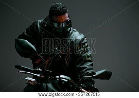 Selective Focus Of Armed Bi-racial Cyberpunk Player In Mask And Futuristic Glasses Holding Gun And R