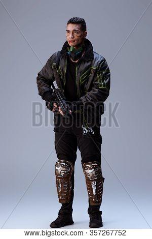 Handsome Bi-racial Cyberpunk Player Holding Gun And Standing On Grey