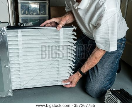 Senior Caucasian Man Checking A Clean Folded Air Filter In The Hvac Furnace System In Basement Of Ho