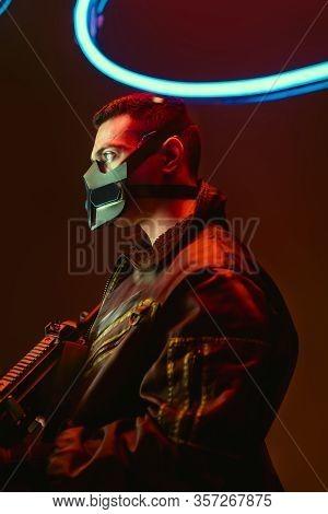 Bi-racial Cyberpunk Player In Mask Holding Gun Near Blue Neon Lighting On Black