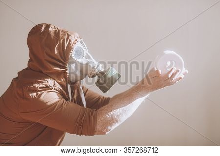 Man in a gas mask holds a roll of toilet paper. Concept: lack of toilet paper in supermarkets and lo