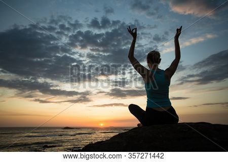 Silhouette of woman doing yoga exercises on the sea coast at twilight.