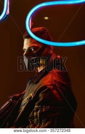 Selective Focus Of Dangerous Bi-racial Cyberpunk Player In Mask Holding Gun Near Blue Neon Lighting