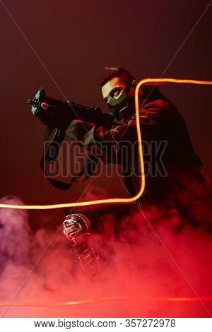 Dangerous Bi-racial Cyberpunk Player In Protective Mask Aiming Gun Near Neon Lighting On Black With