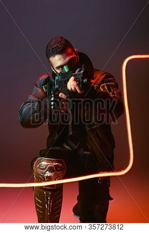 Bi-racial Cyberpunk Man In Mask Aiming Gun Near Neon Lighting On Black