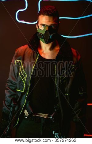 Bi-racial Cyberpunk Player In Protective Mask Holding Gun Near Blue Neon Lighting On Black