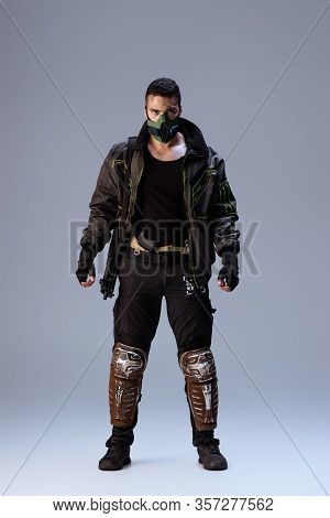 Mixed Race Cyberpunk Player In Mask Standing On Grey