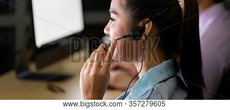 Asian young adult confidence operator colleague team with headsets working in a call center at night as customer service and technical support. Using as Late night hard working 24 Hr. 7 Days concept.