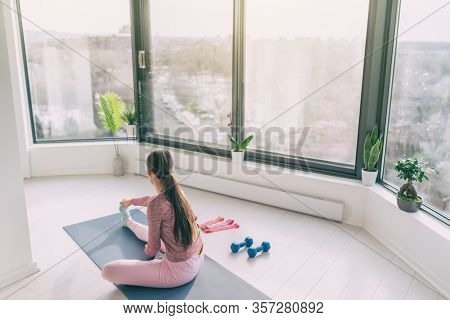 Home fitness yoga workout woman exercising at home stretching legs warm up training. Fit girl working out in morning sunlight in living room of apartment house.