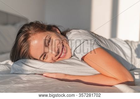 Happy home relaxation asian smiling woman staying in bed relaxing in bedroom candid portrait. Natural beauty healthy skincare model face. Comfortable foam mattress and pillow.