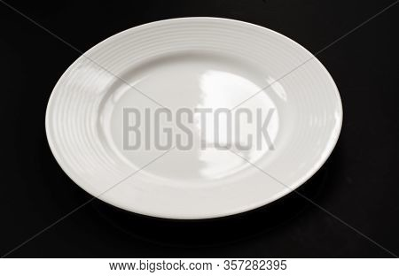 One White Plate On Black Background Closeup.  This Clean White Glass Empty Dish Is A Glass Object Wi