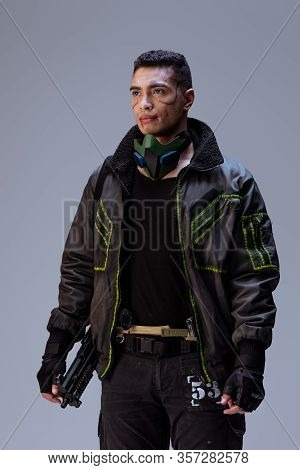 Handsome And Armed Bi-racial Cyberpunk Player Standing On Grey