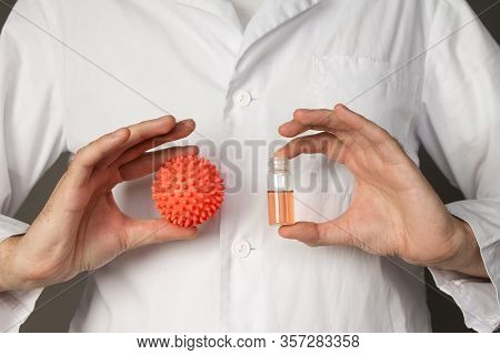 A Medical Worker Holds A Model Of The Coronavirus. Photo On A Grey Background