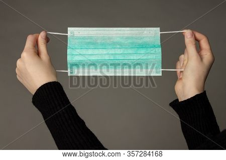 Girl Is Holding A Three-layer Disposable Medical Mask For Respiratory Protection. Photo On A Grey Ba