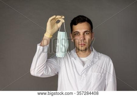 The Doctor Holds And Puts On A Medical Mask To Protect Himself From A New Virus - The Coronavirus. P