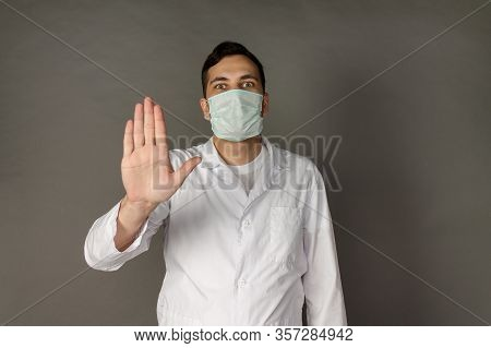 Portrait Of A Doctor In A Medical Gown Clutching His Head Because Of The Number Of Patients With Cor