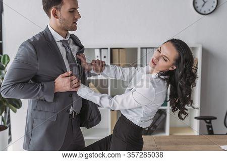 Displeased Secretary Pushing Away Businessman Molesting Her In Office