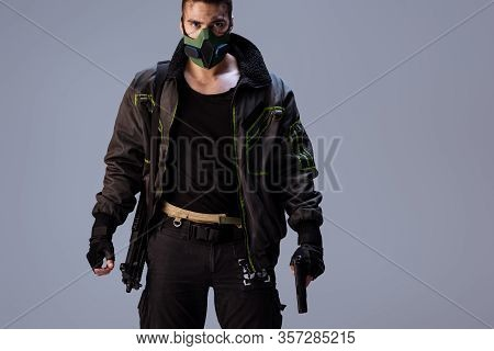 Armed Mixed Race Cyberpunk Player In Mask Standing Isolated On Grey