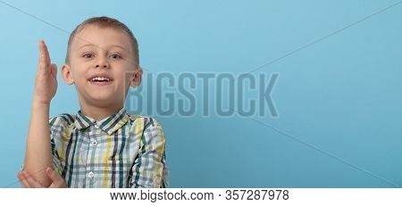 The Boy Reaches Up. The Guy Reaches Out To Answer At The Board. A Boy In A Plaid Shirt On A Blue Bac