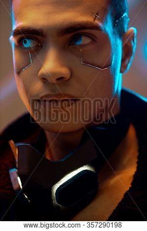 Bi-racial Cyberpunk Player With Metallic Plates On Face Looking Away Near Neon Lighting