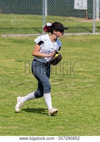 Fast Pitch Softball Outfielder Wearing Sunglasses Handling A Ball In Play On The Grass In The Outfie
