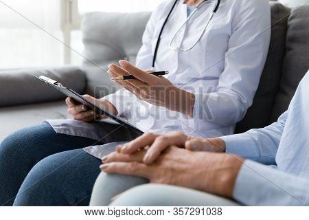 Female Doctor Consult Sick Senior Patient At Home