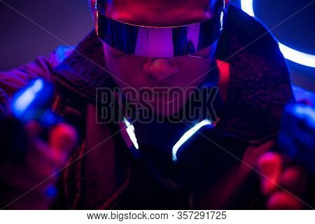 Selective Focus Of Armed Bi-racial Cyberpunk Player In Futuristic Glasses Holding Guns Near Neon Lig