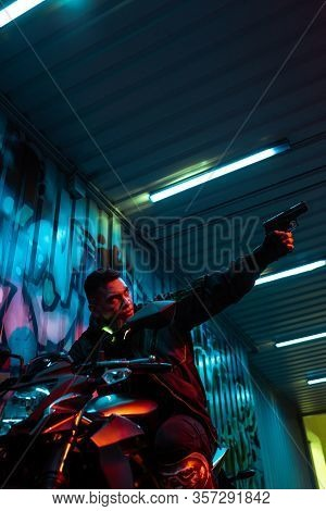 Low Angle View Of Mixed Race Cyberpunk Player On Motorcycle Aiming Gun