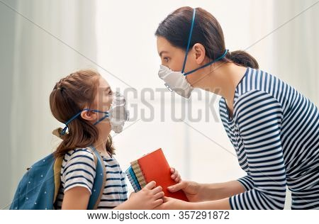 Mother and child wearing facemasks during coronavirus and flu outbreak. Virus and illness protection, home education and quarantine. COVID-2019