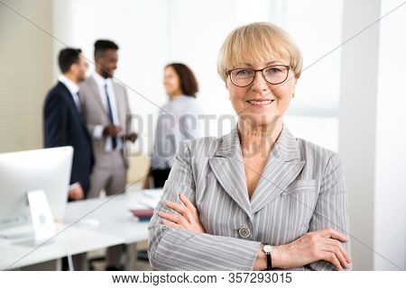 Portrait of happy successful mature business woman in an office with colleagues on the background