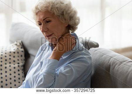 Sick Old Lady Sit On Couch Suffering From Neck Pain