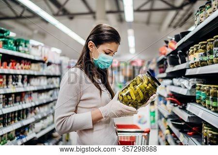 Woman With Hygienic Mask Shopping For Supplies.cpandemic Quarantine Preparation.choosing Nonperishab