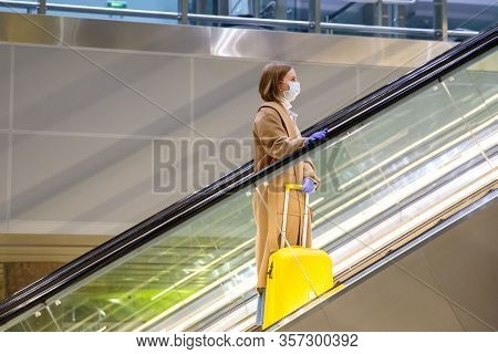 Woman With Yellow Luggage Stands On Escalator, Holds Escalator Handrail In Airport Terminal Through