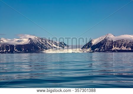 A View Of The Arctic Island From The Sea, Beyond The Ocean, You Can See The Shore, The Mountains Cov