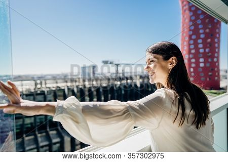 Smiling Young Business Woman Opening Up A Window For The View.hotel Room In Business/industrial Area