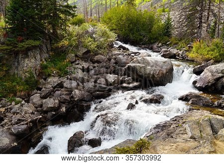 A Beautiful Mountain Waterfall Runs Through A Forest With The Changing Colors Of Autumn.