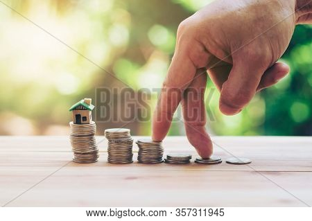 House Placed On Coins Men's Hand Is Planning Savings Money Of Coins To Buy A Home