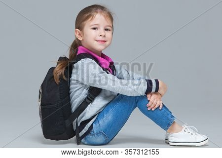 Primary School Girl In Jeans And Uniform Jacket With Backpack Is Sitting On The Floor. Isolated On G