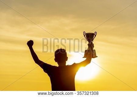 Winner Win Holding Golden Champion Trophy Cup Prize. Silhouette Best Award Victory Trophy For Profes